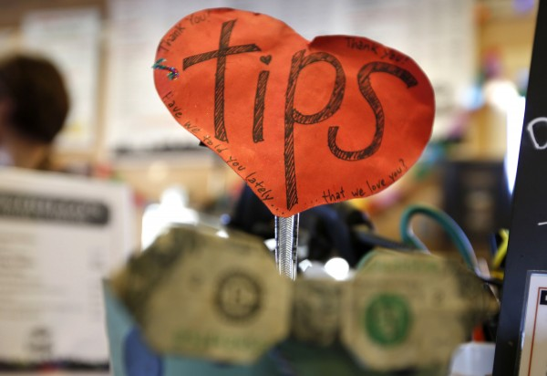 A sign reads, &quotHave we told you that we love you?&quot on the tip jar at Coffee By Design on Washington Street in Portland.