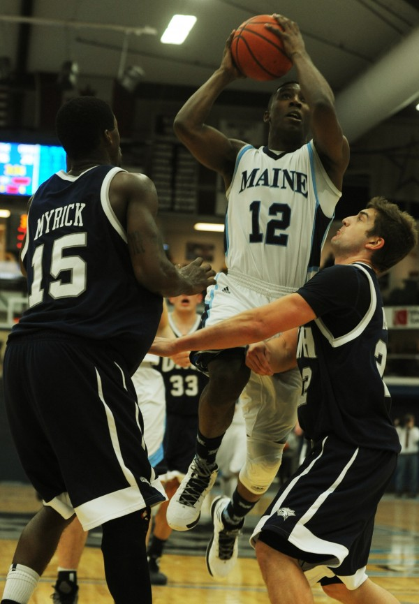 UMaine's Xavier Pollard splits the New Hampshire defense Ferg Myrick (left) and Scott Morris (right) during first half action at Orono on Wednesday, Jan. 30, 2013.