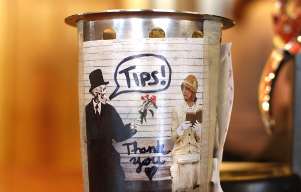 A skeleton offers flowers to a woman reading a book in a picture used to decorate the back side of a tip jar at Spartan Grill in Portland's Monument Square.