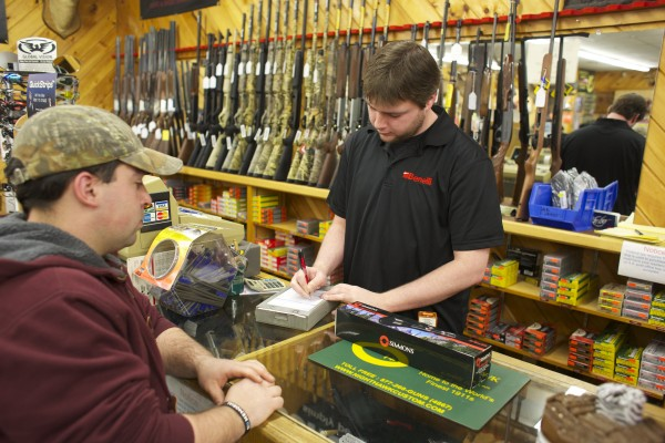 Chris Luce (left) buys a .22 caliber rifle from Bob Fennell Wednesday afternoon at Van Raymond Outfitters in Brewer. President Barack Obama announced proposals to reduce gun violence Wednesday morning.