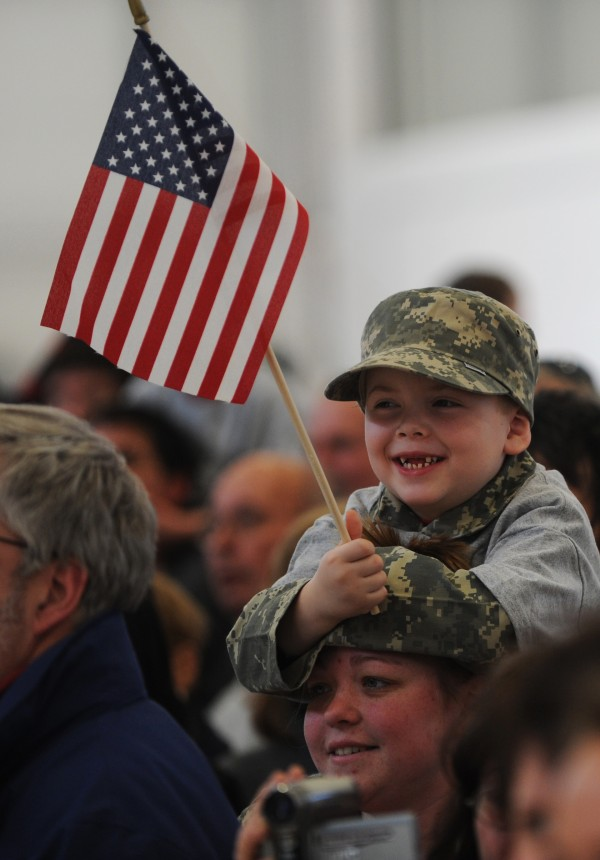 William Hisler of Ellsworth sits atop his mother's shoulders as he waits with other family members for his father, Will, who has been deployed with the Maine Army National Guard