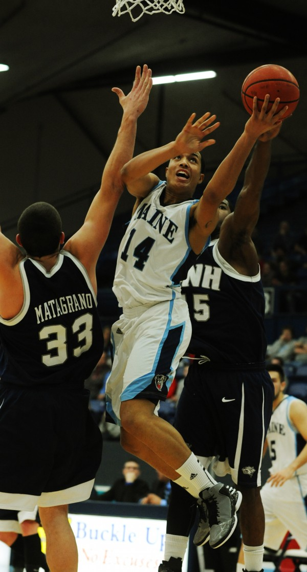 UMaine's Justin Edwards splits the UNH defense Chris Matagrano (left) and Ferg Myrick (right) during first half action at Orono on Wednesday, Jan. 30, 2013.
