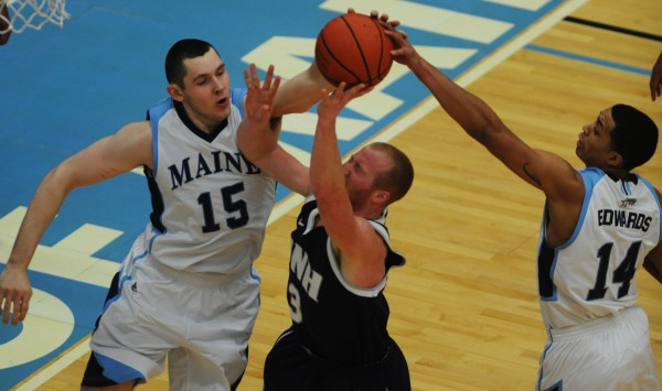 UMaine's Alasdair Fraser (left) and Justin Edwards (right) deny UNH's Chadler Rhoads a shot during first half action at Orono on Wednesday, Jan. 30, 2013.