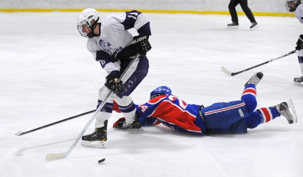 Messalonskee High School's Tyler Simpson (right) falls on the ice as he battles for the puck with Hampden Academy's Dylan Cray during the second period of the game in Brewer Wednesday.