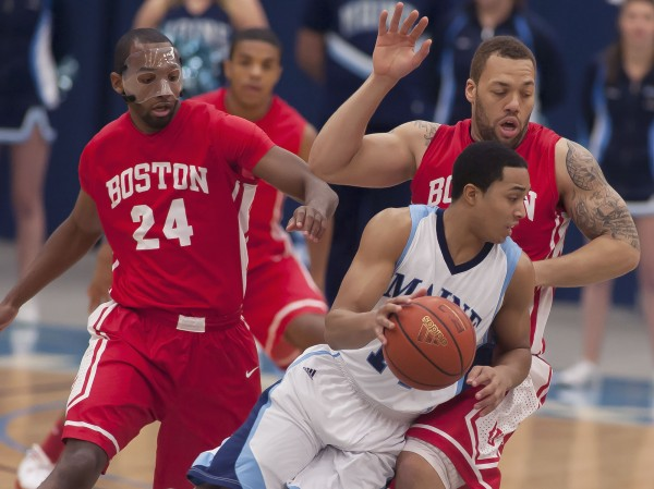 Maine Men's basketball player Justin Edwards (14) drives around BU players Travis Robinson (24) and Dom Morris (15) in the first half of an NCAA college basketball game in Orono on Wednesday, Jan. 2, 2013.