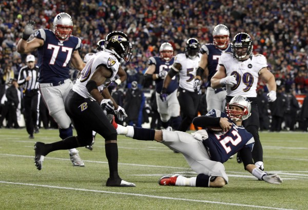 New England Patriots quarterback Tom Brady (12) slides to avoid a hit from Baltimore Ravens free safety Ed Reed (20) during the second quarter of the AFC championship game at Gillette Stadium on Jan. 20, 2013.