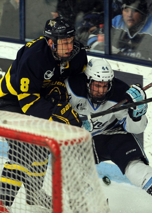 University of Maine's Conor Riley (right) is checked by Merrimack's Brian Christie in the first period of the Black Bears game against Merrimack College Friday night, Jan. 18, 2013, at Alfond Arena.