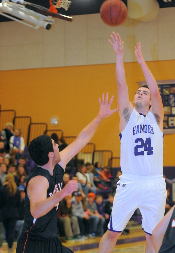 Hampden Academy's Tyler Norris (right) goes up for a shot over Brunswick High School's Bradford Smith during the first half of the game in Hampden on Friday evening, Jan. 11, 2013.