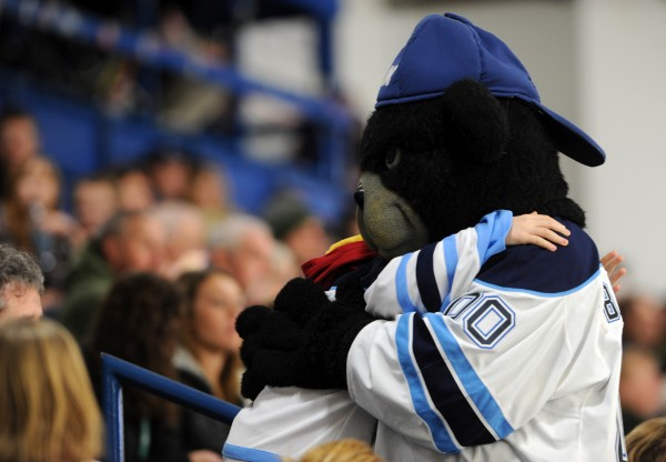 University of Maine's mascot Bananas T. Bear gets a hug from a fan during Friday night's game against Merrimack College.