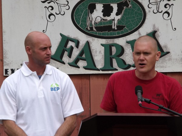 Adam Wintle (left), managing partner for Biogas Energy Partners, and Travis Fogler, Stonyvale Farm dairy operations manager, speak to a crowd about the unveiling of their anaerobic digestion system at Stonyvale Farm in Exeter on Thursday, June 7, 2012.
