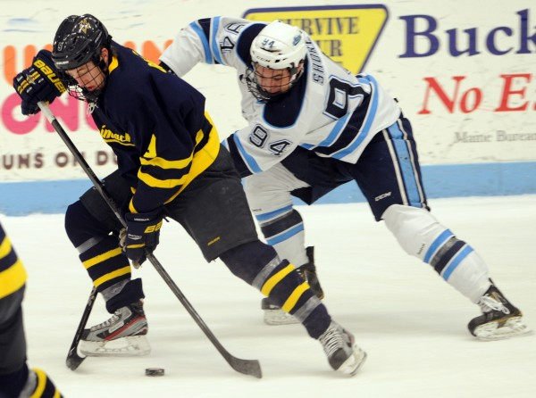 University of Maine's Devin Shore (right) gets around Merrimack's Shawn Bates for the puck in first period action of the Black Bears game Friday night, Jan. 18, 2013, at Alfond Arena.