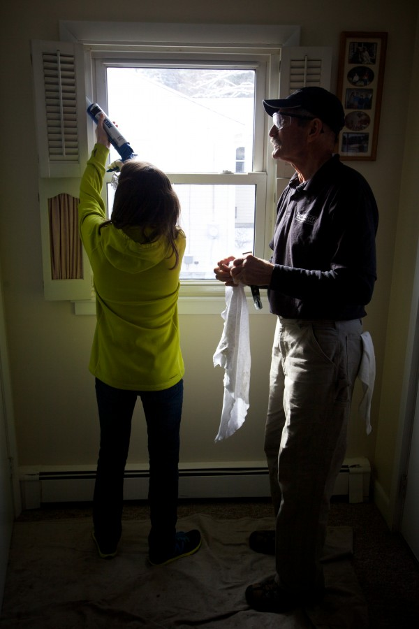 Tom Wojcik shows Haile Cummings how to caulk a window as Brunswick Junior High School students, working with professionals from Upright Frameworks, perform energy efficiency upgrades to a small group home run by the Independence Association in Brunswick on Tuesday, Jan. 29, 2013.