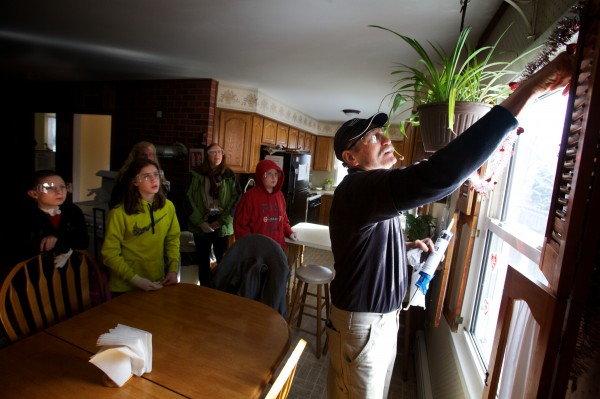 Tom Wojcik demonstrates how to caulk a window as Brunswick Junior High School students, working with professionals from Upright Frameworks, perform energy efficiency upgrades to a small group home run by the Independence Association in Brunswick on Tuesday, Jan. 29, 2013.