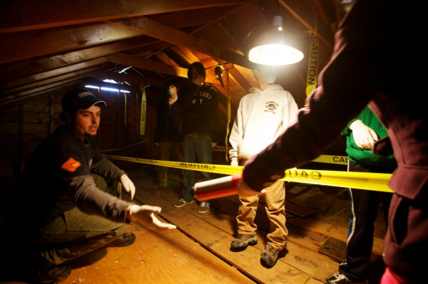 Jake Rackliff (left) shows how to insulate an attic as Brunswick Junior High School students, working with professionals from Upright Frameworks, perform energy efficiency upgrades to a small group home run by the Independence Association in Brunswick on Tuesday, Jan. 29, 2013.