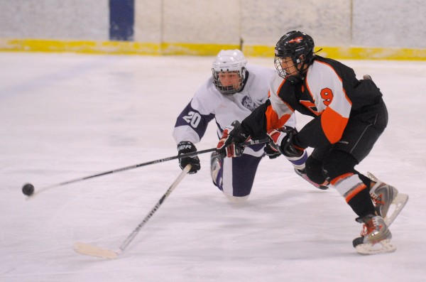 Skowhegan's Anthony James Paul (right) and Hampden's Robert Stowe battle for the puck during the game in Brewer on Wednesday, Jan. 9, 2013.
