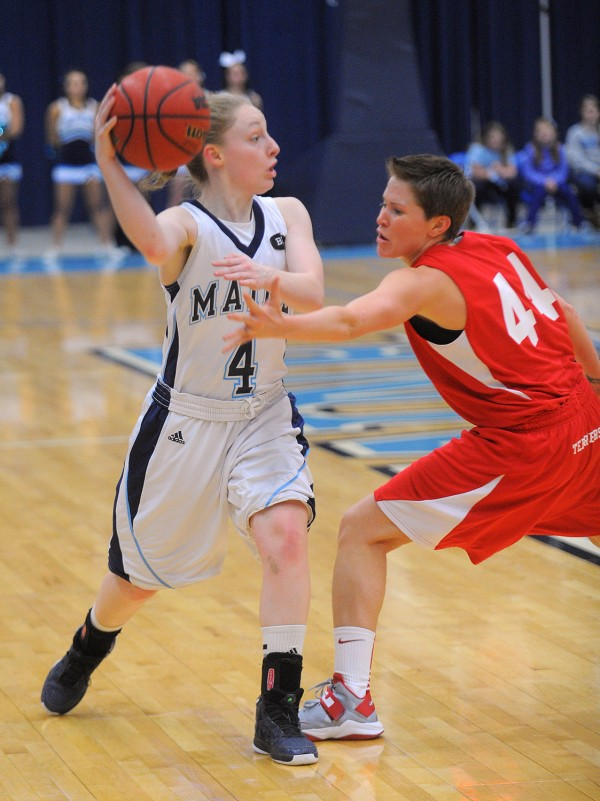 The University of Maine's Courtney Anderson (left) looks to make a pass over Boston University's Mo Moran during the first half of the game in Orono on Wednesday might.