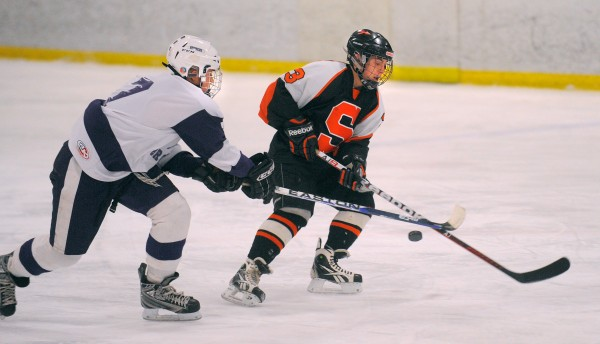Hampden's Sam Ward (left) and Skowhegan's Kyle Demchak battle for the puck during the game in Brewer on Wednesday, Jan. 9, 2013.