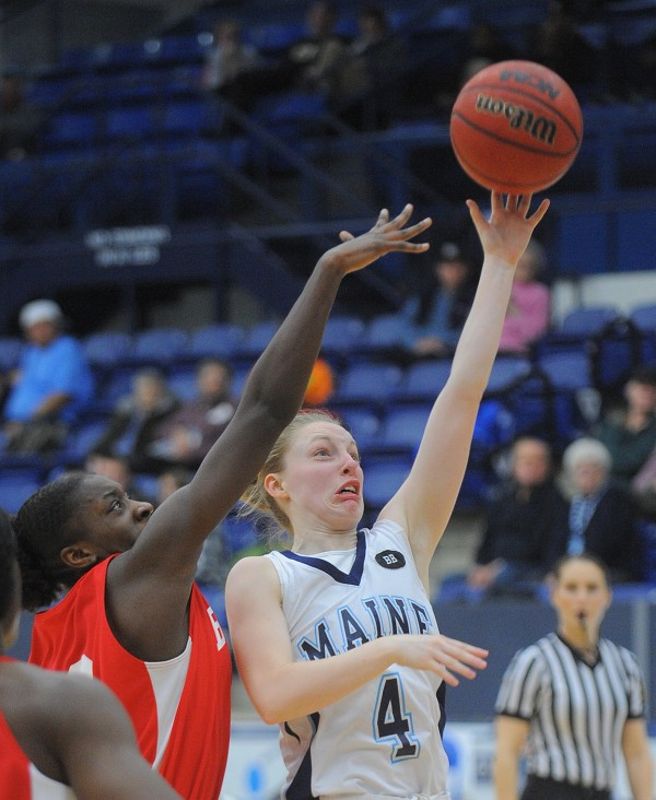 The University of Maine's Courtney Anderson (right) shoots while under pressure from Boston University's Chantell Alford during the first half of the game in Orono on Wednesday night.