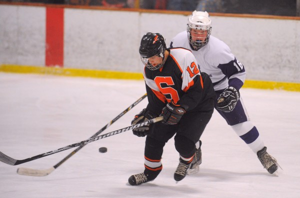 Skowhegan's Kameron Nelson (left) Hampden's Will Manning battle for the puck with during the game in Brewer on Wednesday, Jan. 9, 2013.