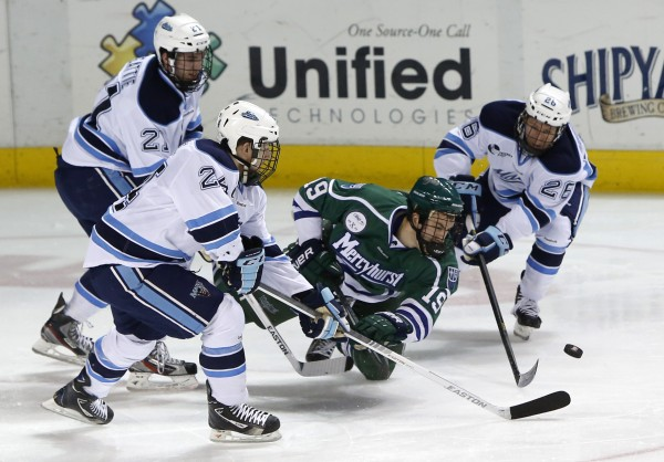 Mercyhurst's Matthew Zay gets knocked off the puck by Maine's Mark Anthoine (left) and Adam Shemansky (right) in the second period at the Cumberland County Civic Center, Friday, Jan 4, 2013, in Portland, Maine. Maine's Kyle Beattie follows at rear.