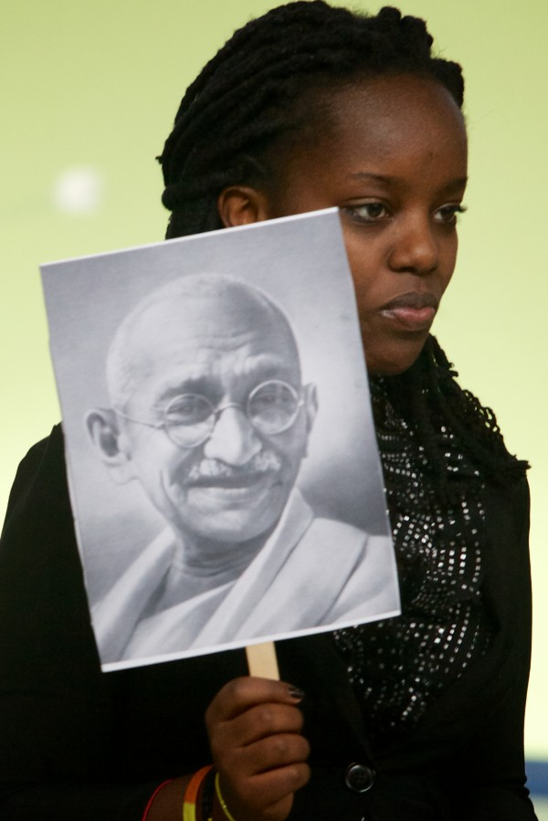 Aline Cyuzuzo holds a picture of Mahatma Gandhi, a major influence on Dr. Martin Luther King, during a staged reading of the book &quotMartin's Big Words&quot at the Ocean Avenue Elementary School's Martin Luther King Day event Monday, Jan 21, 2013.