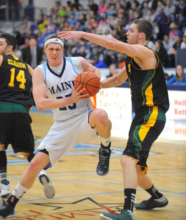 The University of Maine's Till Gloger (left) drives on the University of Vermont's Ethan O'Day during the first half of the game in Orono Wednesday evening.