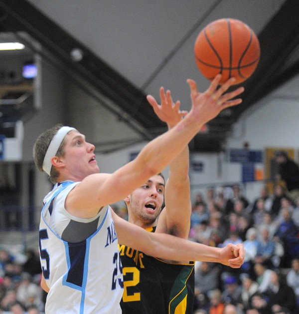 The University of Maine's Till Gloger (left) lays up a shot as the University of Vermont's Ethan O'Day defends during the first half of the game in Orono Wednesday evening.