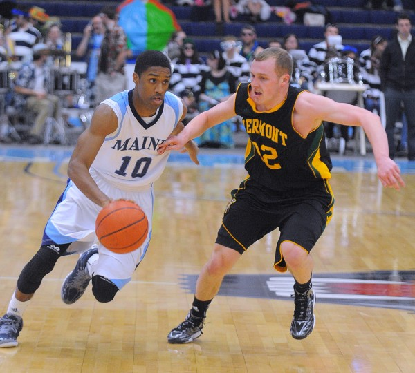 The University of Maine's Shaun Lawton (left) drives on the University of Vermont's Sandro Carissimo during the first half of the game in Orono Wednesday evening.