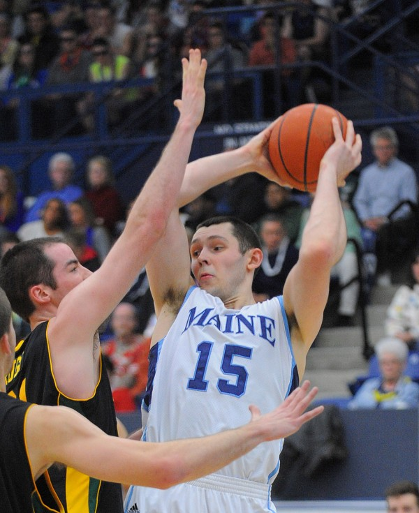 The University of Maine's Alasdair Fraser (right) looks up to pass the ball as the University of Vermont's Clancy Rugg tries to block during the first half of the game in Orono Wednesday evening.