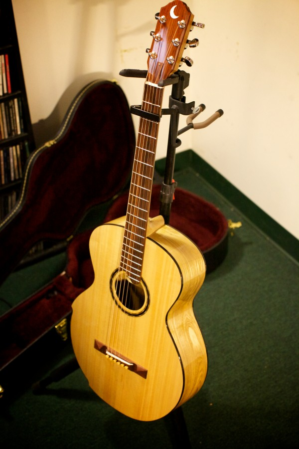 A guitar made from a Universalist Unitarian Church of Brunswick pew which survived a 2011 fire stands in Jud Caswell's home recording studio in Brunswick on Jan. 22, 2013. Caswell used the guitar to record a song he wrote about the fire.