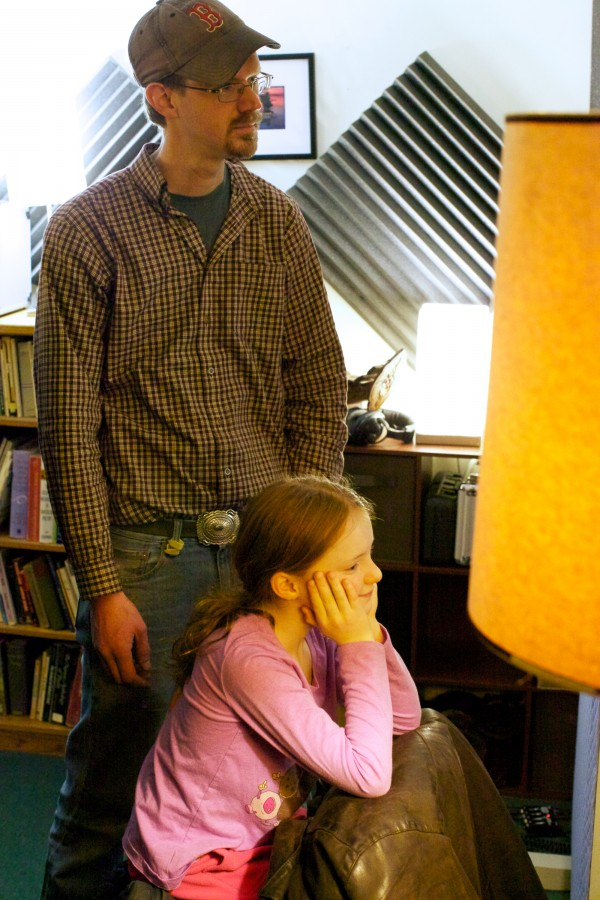 Carter Ruff and daughter Zoe listen through the recording studio window as Jud Caswell records a song he wrote about their church burning down. Caswell is playing a guitar built by Ruff from a surviving pew.