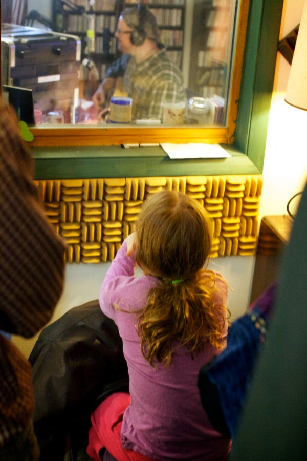Zoe Ruff, 9, listens through the recording studio glass as Jud Caswell records a song he wrote about the Universalist Unitarian Church of Brunswick burning down. Caswell is playing a guitar built by Ruff's father from a surviving pew.