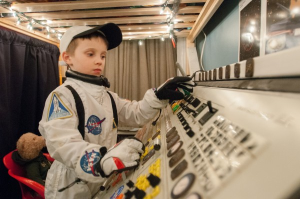 Finn Gorman plays with his NASA space command center his father built for his fifth birthday. Jeremiah Gorman used several used electronics for the cockpit, including an old television station control board.