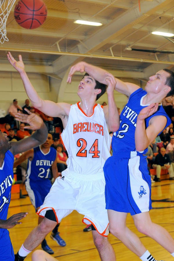 Lewiston High School's Josh Thomas (right) blocks a shot by Brewer High School's Ian Burgess during the first half of the game in Brewer on Friday, Jan. 25, 2013.