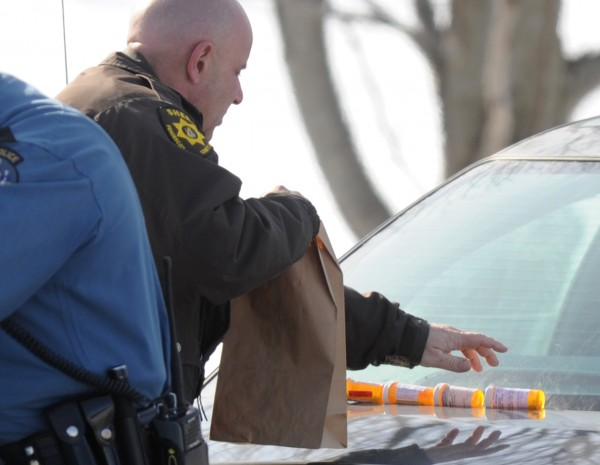 Penobscot County Sheriff's Deputy James Kennedy puts prescription pill bottles into a brown bag while assisting in an ongoing burglary investigation on the Pushaw Road in Bangor on Monday.