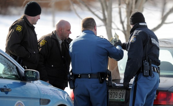 Penobscot County Sheriff's Deputies Steve Saucier (left) and James Kennedy and Maine State Police Troopers Darren Vittum and Tucker Bonnieve put cash into a brown bag on the trunk of a car that was later sealed with evidence tape and towed away from a Bangor residence on the Pushaw Road in Bangor on Monday.