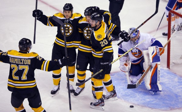 Boston Bruins' Dougie Hamilton (27), Gregory Campbell (second from left), Shawn Thornton (center) and Daniel Paille (20) celebrate after Thornton scored a goal against New York Islanders' goaltender Rick DiPietro in the first period of their NHL hockey game in Boston on Jan. 25, 2013.