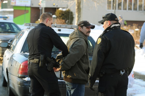 Bangor Police officers Brian Smith (left) and Joe Baillargeon right take John Leonard, 47, of Bangor into custody on Monday, Jan. 7, 2013. Leonard was arrested and charged with criminal threatening with a dangerous weapon.