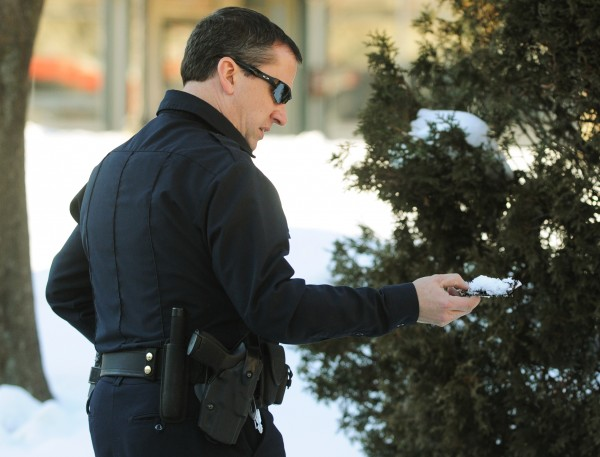 Bangor Police officer Jim Dearing removes what appears to be a folding knife from a snow bank near Pickering Square on Monday, Jan. 7, 2013 after responding to a report of men fighting with a knife in that area.