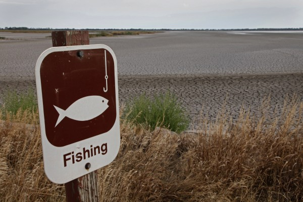 A fishing sign is posted next to one of the dry pools at the Quivira National Wildlife Refuge in Hudson, Kansas in this file photo taken August 7, 2012.  The average temperature in 2012 was 55.3 degrees in the continental United States, topping the previous record for heat set in 1998, the National Oceanic and Atmospheric Administration announced Tuesday.