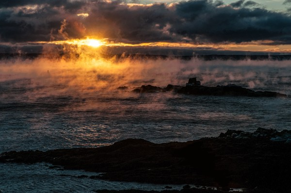 Sea smoke and Sail Rock back lit by sun rising over Grand Manan Island, New Brunswick, Canada. Image taken at Quoddy Head State Park, Lubec, Maine