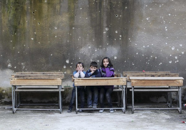 Children sit on school benches at Al-Tawheed school in Aleppo January 1, 2013.