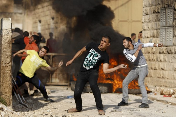 Palestinian protesters throw stones near burning tyres during clashes with Israeli security officers in the West Bank village of Tamoun, near the West Bank city of Jenin January 1, 2013. Clashes broke out after an Israeli military operation in the village on Tuesday.