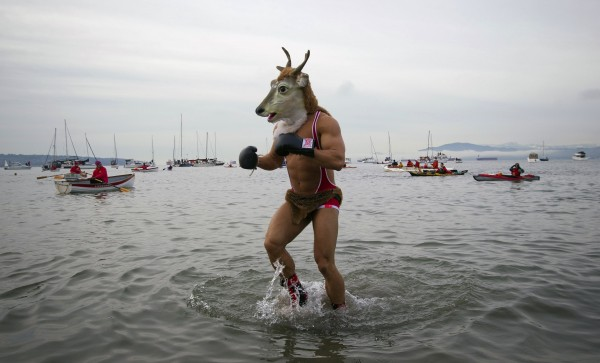 A man wearing a goat mask runs into the English Bay during the annual New Year's Day Polar Bear Swim in Vancouver, British Columbia January 1, 2013.
