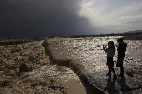 Girls take pictures of water flowing into the Dead Sea during a flash flood near Kibbutz Ein Gedi on Jan. 9, 2013.