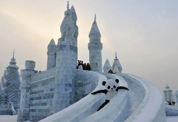 An employee wearing a panda costume slides down from an ice sculpture during the Harbin International Ice and Snow World festival in Harbin, Heilongjiang province, Jan. 11, 2013.