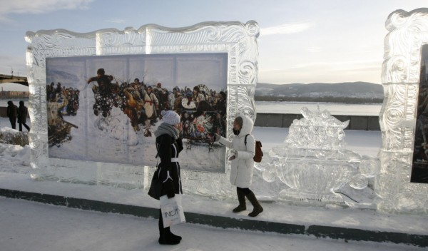 Two girls look at reproductions of work by Russian classical painter Vasily Surikov, displayed in ice frames, during the 1st International festival of snow and ice sculpture called &quotThe Magical Ice of the Siberia&quot on a bank of the Yenisei River in Krasnoyarsk, Jan. 14, 2013. According to the festival organizers, teams of ice and snow sculptors from USA, China, Kazakhstan and from 25 cities in Russia are taking part in the 5-day competition which starts on Monday.