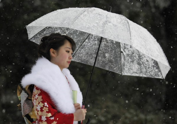 A Japanese woman in kimono attends a ceremony celebrating Coming of Age Day in heavy snowfall at Toshimaen amusement park in Tokyo on Jan. 14, 2013. Youths across Japan are honored with special coming-of-age ceremonies when they reach the age of 20. Tokyo saw its first snowfall this season on Monday. Transportation has been affected by the weather with some flights to and from the capital's Haneda airport being cancelled, parts of the expressways have temporarily closed and local train services have been delayed.