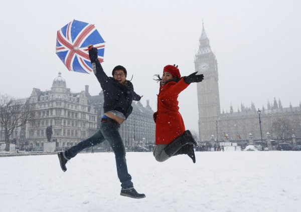 Pandu and Dian, tourists from Indonesia, jump for a souvenir photograph taken by their friend in front of the Houses of Parliament, during a snowfall in central London January 20, 2013.