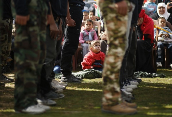A girl watches Palestinian students demonstrate their skills during a graduation ceremony for a martial arts course organized by Hamas ministry of education in Gaza City on Jan. 24, 2013.